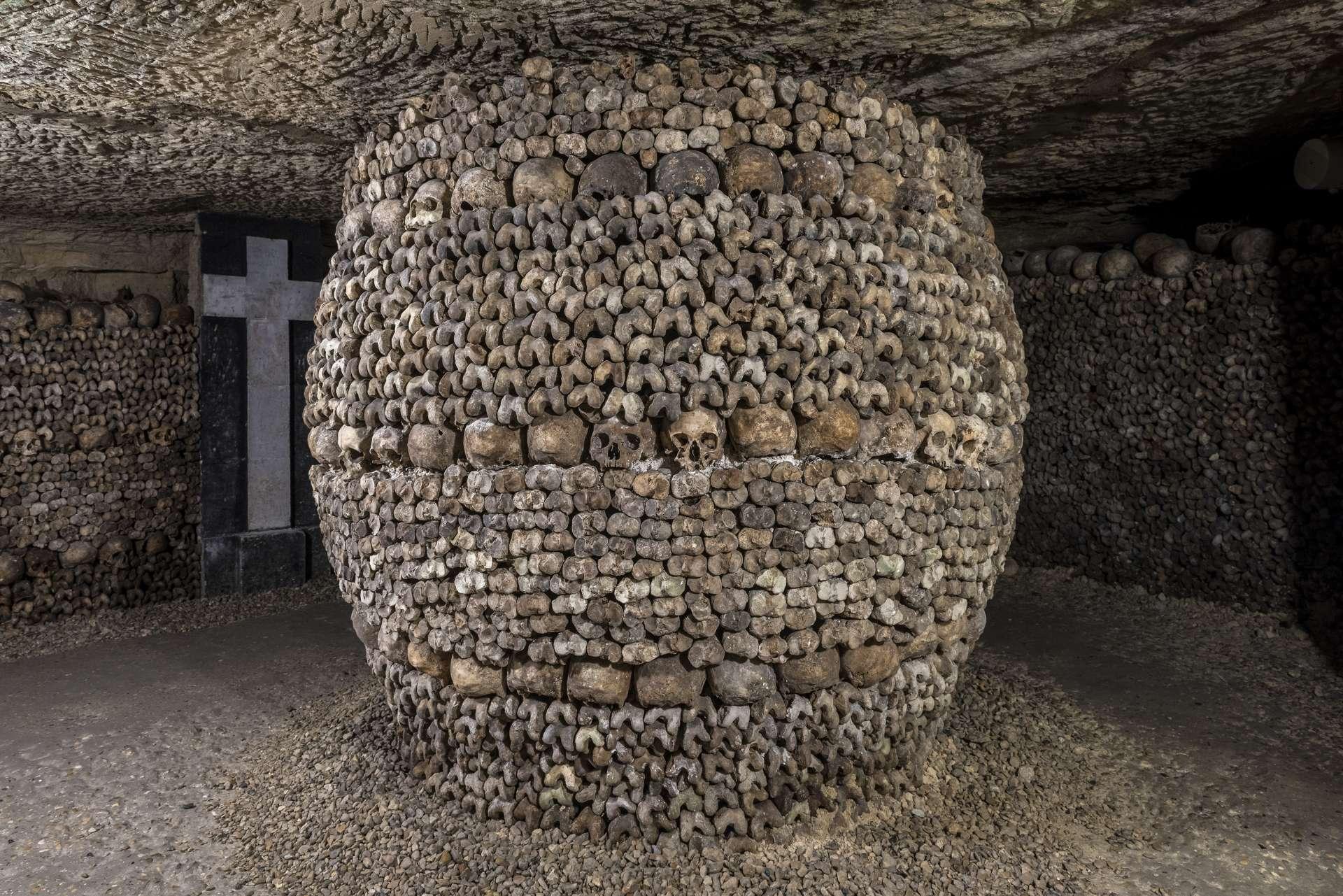 France - Paris - Catacombes - Dans la «crypte de la passion», le pilier de soutènement est masqué par un habillage de crânes et de tibias en forme de tonneau.