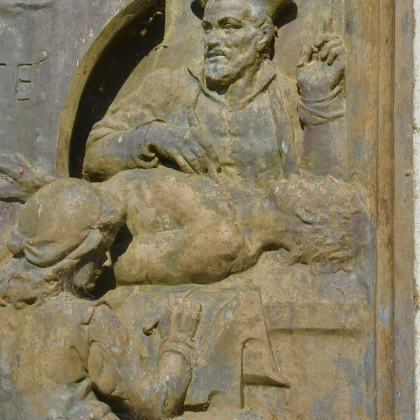 Sur le socle de la statue de Chinon, un relief en bronze souligne la vocation médicale de Rabelais.